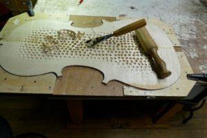 Hakken tot de gaatjes in het onderblad van de cello weg zijn